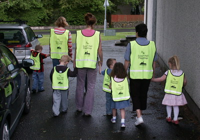 The children & their carers set out on a walk wearing their new safety vests